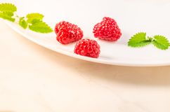 Raspberry and mint. Healthy juicy ripe organic raspberry fruit and mint leaves close-up, on white bowl. Sweet dessert stock images