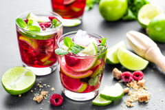 Raspberry mojito cocktail with lime, mint and ice, cold, iced refreshing drink or beverage closeup. Raspberry mojito cocktail with lime, mint and ice, cold, iced stock images