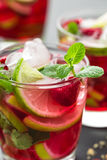 Raspberry mojito cocktail with lime, mint and ice, cold refreshing drink. On black background Royalty Free Stock Images