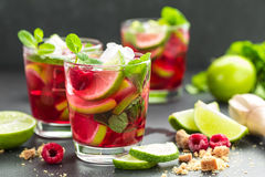 Raspberry mojito cocktail with lime, mint and ice, cold refreshing drink. On black background Royalty Free Stock Photography