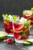 Raspberry mojito cocktail with lime, mint and ice, cold refreshing drink. On black background Stock Photos