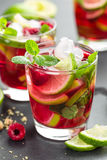 Raspberry mojito cocktail with lime, mint and ice, cold refreshing drink. On black background Royalty Free Stock Image