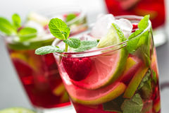 Raspberry mojito cocktail with lime, mint and ice, cold refreshing drink. On black background Royalty Free Stock Photos