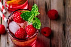 Raspberry Mojito Lemonade with lime and fresh mint in glass on wooden background. Summer refreshing cocktail Stock Photography