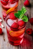 Raspberry Mojito Lemonade with lime and fresh mint in glass on wooden background. Summer refreshing cocktail Stock Images