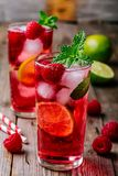 Raspberry Mojito Lemonade with lime and fresh mint in glass on wooden background. Summer refreshing cocktail Stock Photo