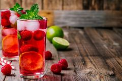 Raspberry Mojito Lemonade with lime and fresh mint in glass on wooden background. Summer refreshing cocktail Royalty Free Stock Image