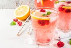 Raspberry mojito or lemonade. Summer refreshing drinks, fruit and berry raspberry mojito or lemonade with fresh mint, frozen raspberries, slices of lemon, ice Stock Image