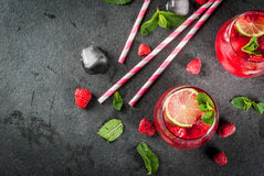 Raspberry mojito lemonade. Summer refreshing non-alcoholic cocktails. Fruit drinks. Raspberry mojito lemonade with fresh organic mint and lime. On a black stone Royalty Free Stock Images