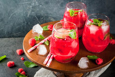 Raspberry mojito lemonade. Summer refreshing non-alcoholic cocktails. Fruit drinks. Raspberry mojito lemonade with fresh organic mint and lime. On a black stone Stock Photo