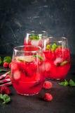 Raspberry mojito lemonade. Summer refreshing non-alcoholic cocktails. Fruit drinks. Raspberry mojito lemonade with fresh organic mint and lime. On a black stone Stock Image