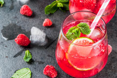Raspberry mojito lemonade. Summer refreshing non-alcoholic cocktails. Fruit drinks. Raspberry mojito lemonade with fresh organic mint and lime. On a black stone Royalty Free Stock Photography