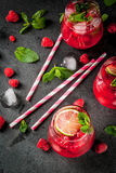 Raspberry mojito lemonade. Summer refreshing non-alcoholic cocktails. Fruit drinks. Raspberry mojito lemonade with fresh organic mint and lime. On a black stone Royalty Free Stock Image