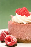 Raspberry mousse cake. Topped with fresh whipped cream on a green background Royalty Free Stock Photo