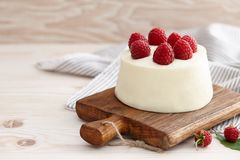 Raspberry mousse cake with fresh raspberries. On wooden board Stock Images