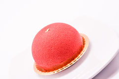 Raspberry mousse cake. With jelly insert, topped with red cocoa butter spray and gold leaves Royalty Free Stock Images