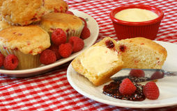 Raspberry Muffins and Berries. A full plate of fresh baked raspberry muffins sit beside a cut muffin with butter, raspberry jam and fresh raspberries Stock Images