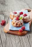 Raspberry muffins. Homemade muffins with a fresh raspberries on dark wooden background, selective focus Royalty Free Stock Images