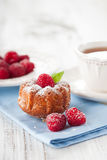 Raspberry muffins. Homemade muffin with a fresh raspberries and cup of tea on white wooden background, selective focus Royalty Free Stock Photos