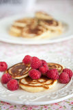 Raspberry pancakes. Delicious small pancakes with raspberries on a small plate stock images