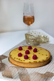 Raspberry and passion fruit tart. On a table near a glass of rose wine stock photography