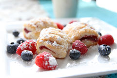 Raspberry pastries with blueberries and raspberries on plate Stock Photos