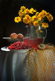 Raspberry, peaches and bouquet from yellow camomiles. Still-life with a raspberry, peaches, compote and a bouquet of yellow camomiles stock image