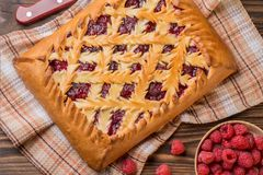 Raspberry pie on a wooden table. Next to him lies a knife and fresh raspberries in a wooden plate. Rustic style. Top view Royalty Free Stock Image