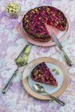 Raspberry and pistachio clafoutis. On a flowered table cloth stock images