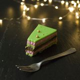 Raspberry-pistachio opera cake slices decorated with with green mirror glaze on black background lights. Pieces of cake look like stock image