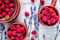Raspberry in pottery and lavender flowers on rustic background t Stock Image