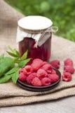 Raspberry preserve and fresh raspberries. Raspberry preserve in glass jar and fresh raspberries Royalty Free Stock Image