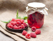 Raspberry preserve and fresh raspberries. Raspberry preserve in glass jar and fresh raspberries on a plate Royalty Free Stock Images