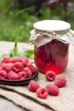 Raspberry preserve and fresh raspberries. Raspberry preserve in glass jar and fresh raspberries on a plate Stock Photography