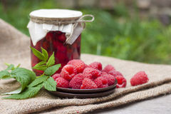 Raspberry preserve in glass jar and fresh raspberries Royalty Free Stock Photography
