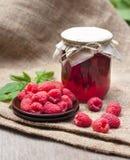 Raspberry preserve in glass jar and fresh raspberries. On a plate Stock Image
