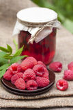Raspberry preserve in glass jar and fresh raspberries Stock Photo