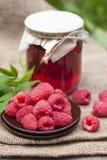 Raspberry preserve in glass jar and fresh raspberries. On a plate Stock Photo