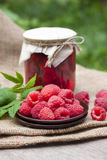 Raspberry preserve in glass jar and fresh raspberries. On a plate Royalty Free Stock Image