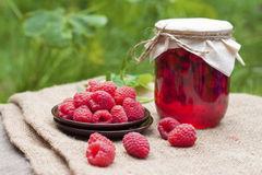 Raspberry preserve in glass jar and fresh raspberries. On a plate Royalty Free Stock Photography
