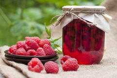 Raspberry preserve in glass jar and fresh raspberries. On a plate Royalty Free Stock Photos