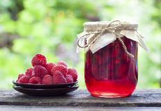 Raspberry preserve in glass jar and fresh raspberries. On a plate Stock Images