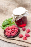 Raspberry preserve in glass jar and raspberries Royalty Free Stock Photos