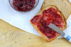 Raspberry preserves in a crystal bowl next to wheat bread spread with the preserves. All on butcher paper with a knife royalty free stock photography