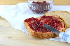Raspberry preserves in a crystal bowl next to wheat bread spread with the preserves. All on butcher paper with a knife stock photo