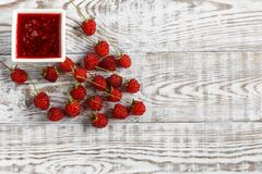 Fresh raspberry and raspberry jam on a wooden background. Copy space. Raspberry and raspberry jam on white boards Royalty Free Stock Photos