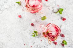 Raspberry Sangria, Lemonade or Mojito. Cold summer drink, Raspberry Sangria, Lemonade or Mojito with fresh Raspberry and syrup, mint leaves, on grey stone Royalty Free Stock Image
