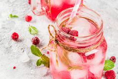 Raspberry Sangria, Lemonade or Mojito. Cold summer drink, Raspberry Sangria, Lemonade or Mojito with fresh Raspberry and syrup, mint leaves, on grey stone Stock Photo
