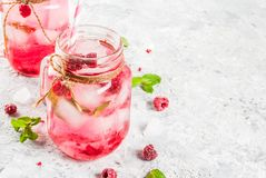 Raspberry Sangria, Lemonade or Mojito. Cold summer drink, Raspberry Sangria, Lemonade or Mojito with fresh Raspberry and syrup, mint leaves, on grey stone Royalty Free Stock Images