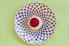Raspberry on a saucer on  white-green background Stock Photos